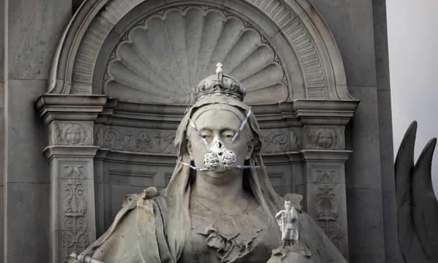 Greenpeace protesters put a face mask on the statue of Queen Victoria opposite Buckingham Palace to highlight air pollution