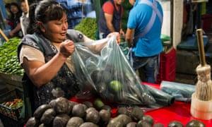 A woman prepares a bag of avocados in Mexico City.