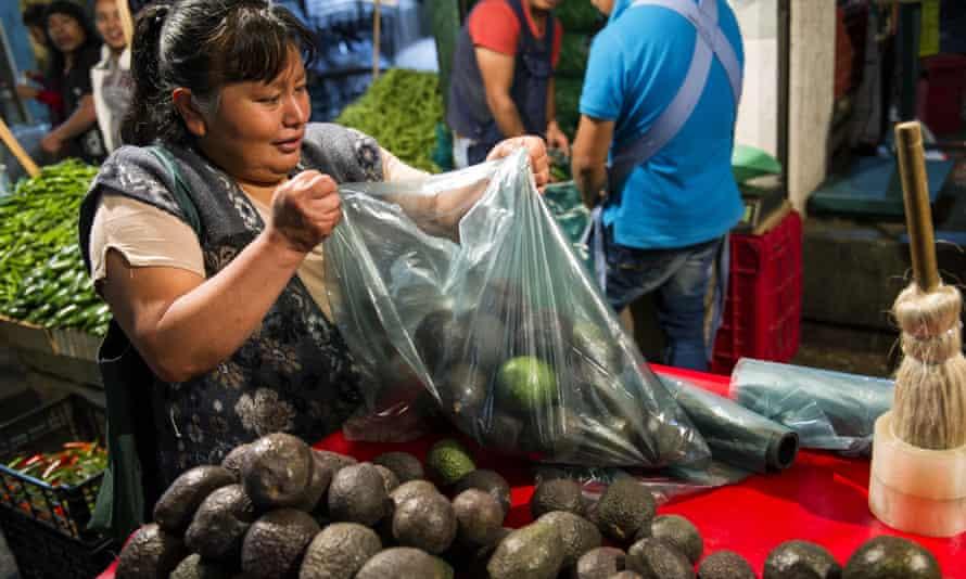 A woman prepares a bag of avocados in Mexico City