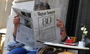 A woman reads the final edition of the Magyar Nemzet newspaper