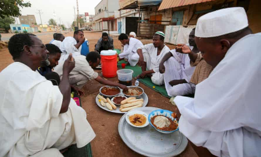 Sudanese men break their fast in a street in the capital Khartoum