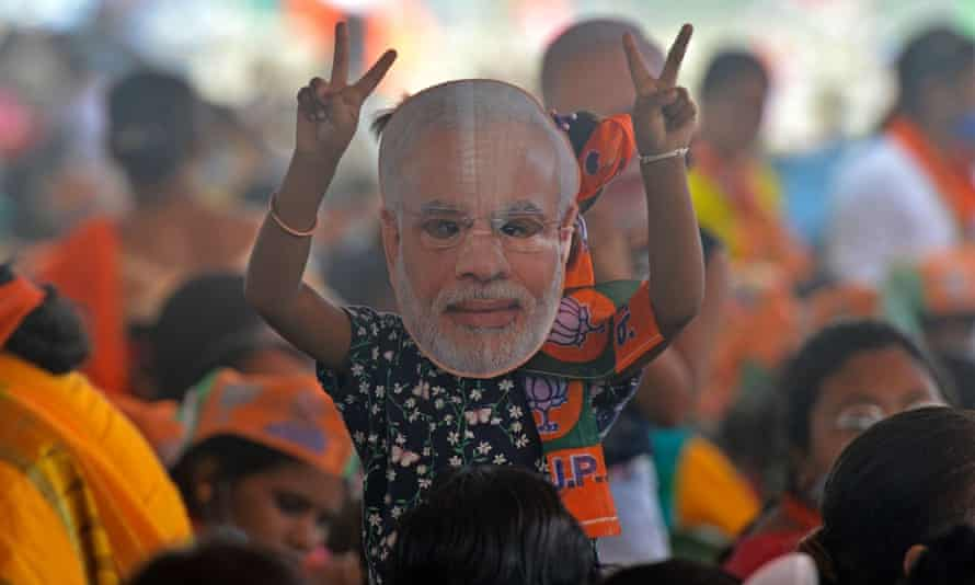 INDIA-POLITICS-VOTEA supporter of Bharatiya Janata Party (BJP) wearing a face cutout of Indian Prime Minister Narendra Modi attends a public rally being addressed by him during the ongoing fourth phase of the West Bengal's state legislative assembly elections, at Kawakhali on the outskirts of Siliguri on April 10, 2021. (Photo by Diptendu DUTTA / AFP) (Photo by DIPTENDU DUTTA/AFP via Getty Images)
