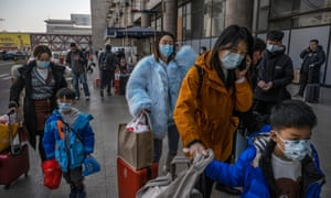 People wear protective masks in Beijing as they arrive to board trains to depart for Lunar New Year celebrations.