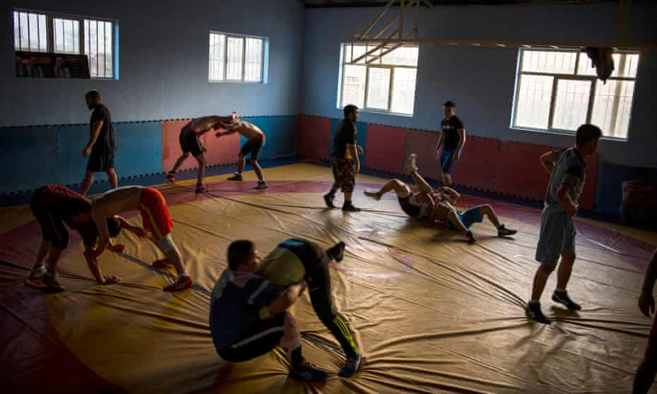 Boys practise wrestling moves on a mat inside the Maiwand wrestling club in Kabul.
