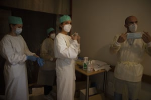 Army healthcare workers suit up before doing their rounds in the Covid-19 ward of a nursing home in Landenne, Belgium