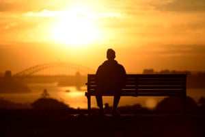 Sydney, AustraliaA man watches the sun set behind Harbour Bridge. Though it's still winter in the country, the city has been experiencing spring-like temperatures