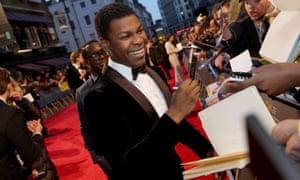 John Boyega signs autographs on the red carpet