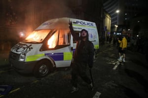Protest against new proposed policing bill, in BristolA demonstrator gestures in front of a burning police vehicle during a protest against a new proposed policing bill, in Bristol, Britain, March 21, 2021. REUTERS/Peter Cziborra