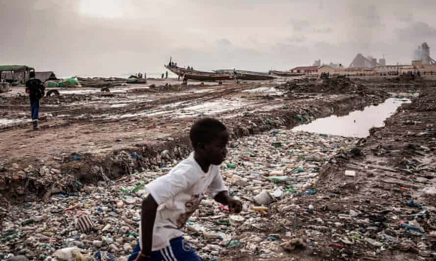 A boy runs past a large pool of putrified water along the coastline in Bargny, Senegal