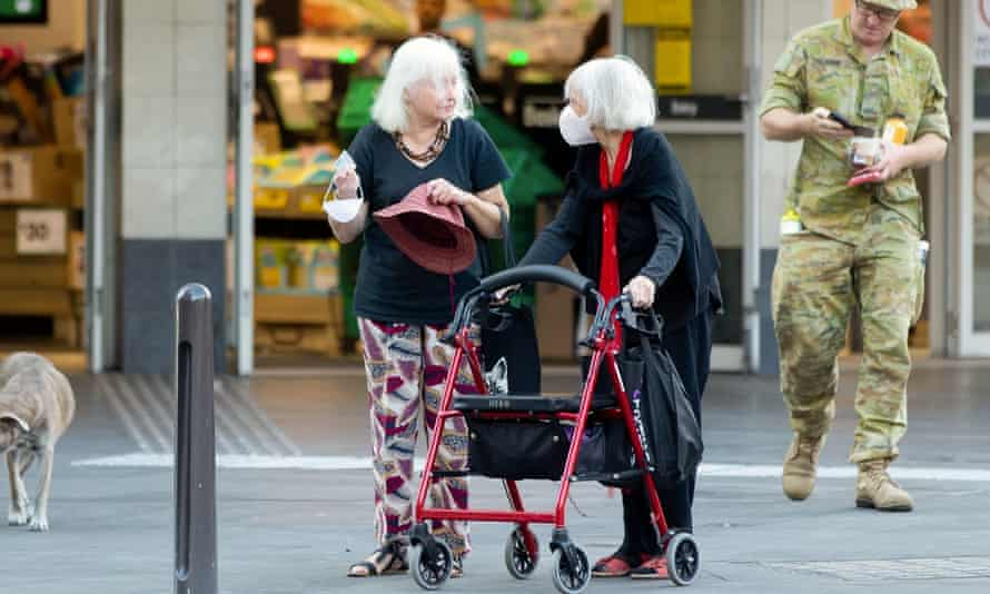 Two women, including one with a walker, chat outside a supermarket in Sydney