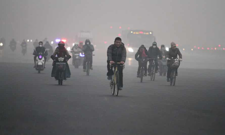 People cycle in heavy smog in Beijing.