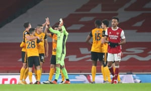 A dejected Pierre-Emerick Aubameyang as Wolves players celebrate victory