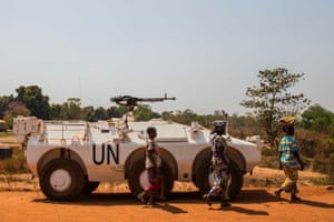 Women walk past a UN armoured personnel carrier at the entrance to the camp in Kaga-Bandoro