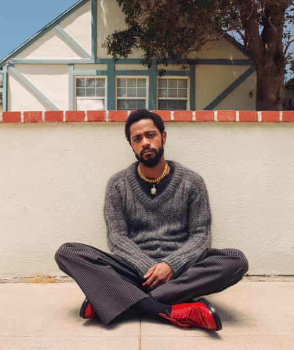Lakeith Stanfield sits cross-legged on a terrace outside