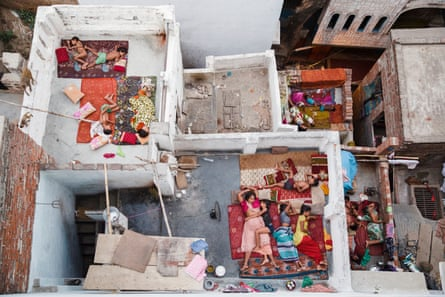 Families sleep on the roof of their homes as temperatures soar in Varanasi, India.