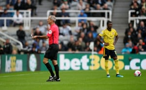 Referee Martin Atkinson removes an object from the pitch.