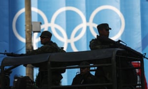 Brazilian soldiers keep watch in front of Olympic rings at the beach volleyball venue ahead of the arrival of the Olympic torch relay in Copacabana on Thursday.