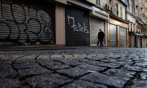 A pedestrian walks down a deserted street in Montmartre, Paris