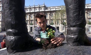 guerrilla gardener plants a flower between the feet of a statue in Parliament Square