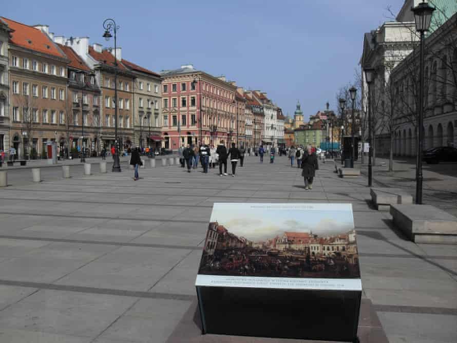 A painting on an information board in front of a the rebuilt Krakowskie Przedmieście Street.