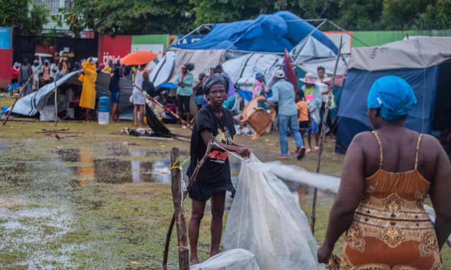 A woman works on a shelter at an improvised refugee camp at Parc Lande de Gabion stadium after Tropical Storm Grace followed a 7.2-magnitude earthquake in Les Cayes, Haiti.