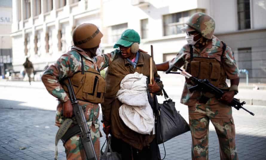 Soldiers escort a homeless woman to a gathering point in Johannesburg