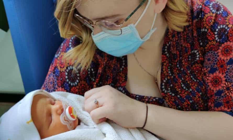 Mother wearing face mask holding new baby