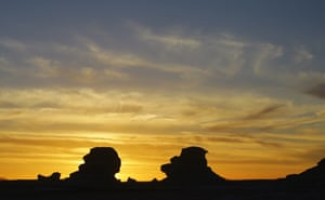 Inselbergs are silhoutted by the setting sun in the desert, about 310 miles (500km) south-west of Cairo