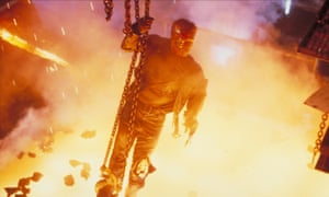 Arnold Schwarzenegger hanging on to a metal chain above a molten pit of metal