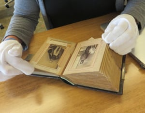 Dr Lynley Wallis from the University of Notre Dame, looking at a carte de visite photograph collection of officers and troopers, at John Oxley library in Brisbane
