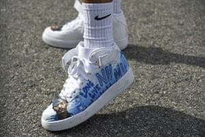 A fan wears shoes in tribute to Nipsey Hussle at the late rapper's memorial service.