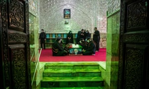 Mourners sit next to the coffin of the Iranian nuclear scientist Mohsen Fakhrizadeh in Tehran