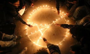 Hands reach into circle to light candles in an image of the Eiffel tower