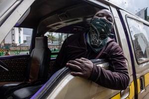 A matatu passenger shows the bandana he wears to protect him from the coronavirus