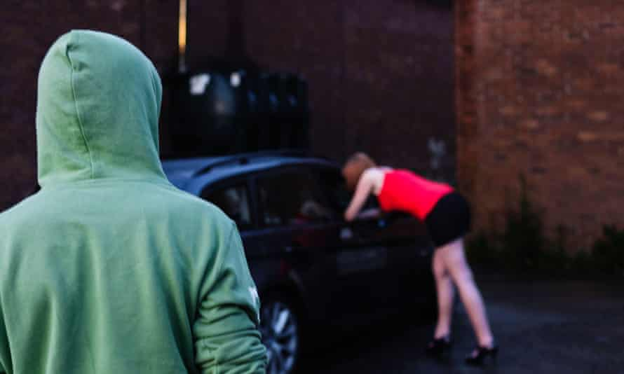 A man watches a sex worker talking to a potential customer in a car (posed by models)