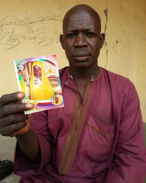 Habiba's father holding a photo of her.
