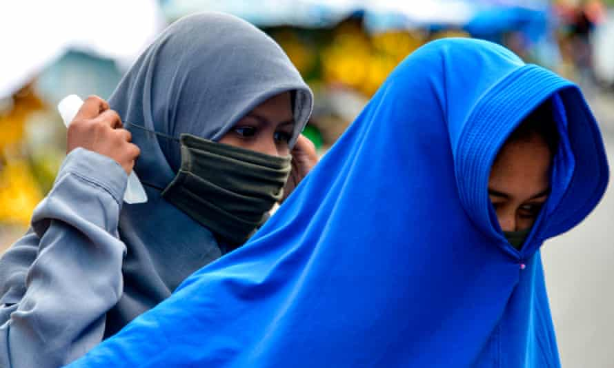 A woman puts on face mask to protect against coronavirus, in Banda Aceh, Indonesia.