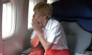 Woman with short hair in airplane seat looking out of the window