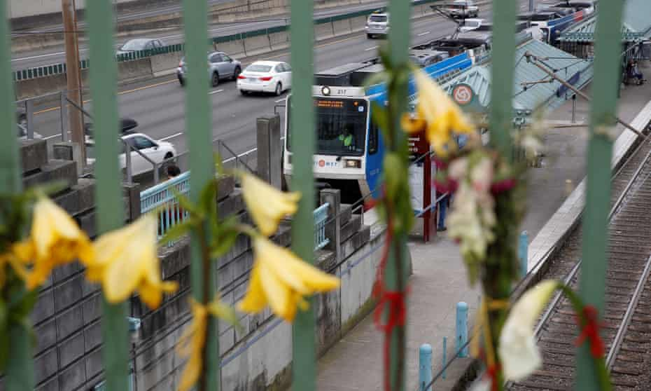 Flowers hang at a makeshift memorial for the two men who were killed on a commuter train in Portland.