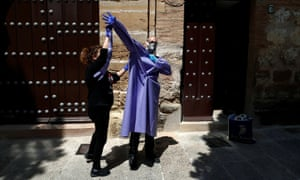 Priest Andres Conde, 49, receives help from his twin sister Inma while donning personal protective equipment he received from a convent, in Ronda, southern Spain April 18, 2020.