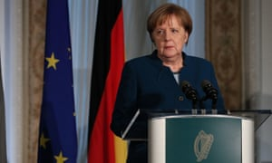 Angela Merkel standing at a microphone with flags in the background