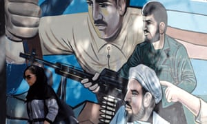 A woman walks past a wall painting depicting Iranian martyrs in Tehran