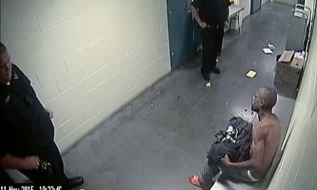 Michael Marshall is seen sitting at right, minutes before being restrained by Denver sheriff's deputies.