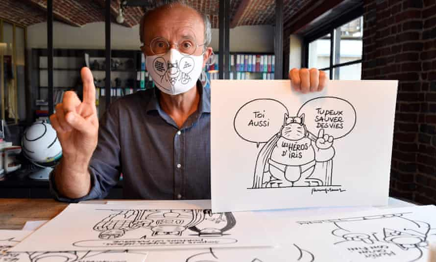 The Belgian cartoonist Philippe Geluck, creator of the comic strip Le Chat (The Cat), poses in his art studio while wearing a protective facemask and cartoons of the comic character, during an interview with AFP about 'the world after' the coronavirus crisis,