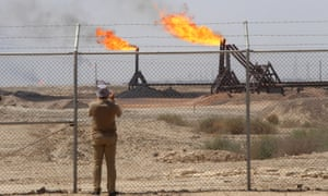 A journalist takes pictures of the West Qurna-1 oilfield, which is operated by ExxonMobil near Basra, Iraq.