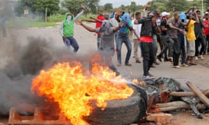Protesters stand behind a burning barricade during protests on a road leading to Harare, Zimbabwe, January 15.