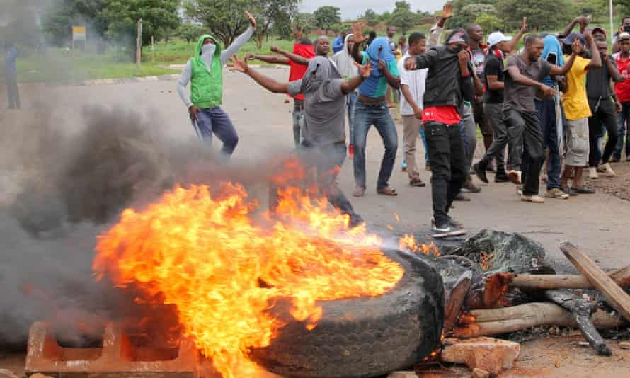 Protesters stand behind a burning barricade during protests on a road to Harare