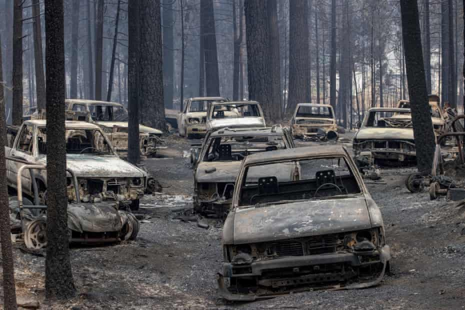 Scorched vehicles destroyed by the Caldor fire rest on Evergreen Drive in Grizzly Flats, California.