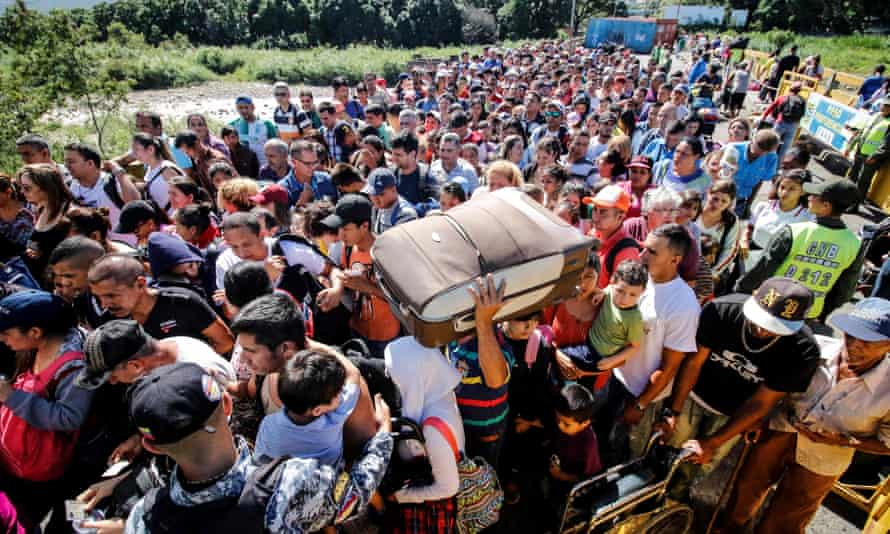 People queue to cross the bridge from San Antonio del Tachira in Venezuela to Cucuta, in Colombia, to buy goods due to supplies shortage in their country