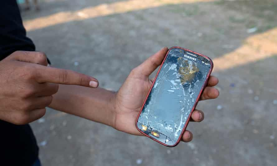 A refugees shows the cracked screen of his mobile phone